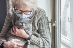 Elderly,Woman,In,Protective,Mask,Holding,A,Cat,Looks,Out